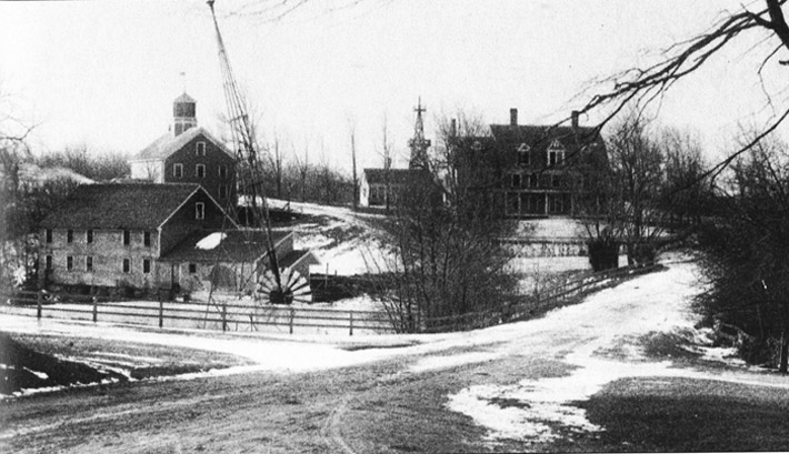 Photo of the old Mill Road bridge before the current stone arch bridge was built. The sawmill on the other side of the river still stands. The house in the background is probably the house that was moved to the other side of Highland St.