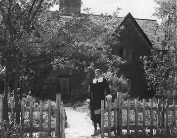 John Updike standing in front of the Whipple House dressed inPuritan garb for Old Ipswich Days