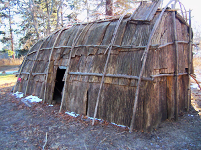 they lived in longhouses, a common building of the Iroquois Nation. Often up to 80 feet long and 20 feet wide, longhouses had openings at both ends covered with animal skins to keep out the cold. Poles were set in the ground and connected to horizontal poles on which large pieces of bark were sewn in place like shingles. Smoke from the central fire pit escaped through holes in the roof. Villages were made up of several longhouses housing multiple generations of each family.