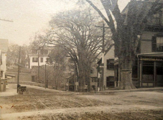 The intersection of South Main and Elm Streets. The Ipswich Savings Bank was on the right. In the distance is the Choate Bridge, a line of small shops at the foot of North Main St., and the Ipswich Female Academy touring over them.