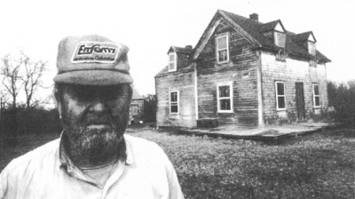 This is a photo of Lew as he stands in front of his house at Grape Island