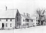 The house on the left in this old photo  is the Caleb Lord House, on the corner of Manning and High Streets It was an early First Period houe. Notice the very steep slope of the roof which hangs over the second story windows, and the massive center chimney. These are traditional charactieristics of Ipswich's Firt Period houses 9built between 1640 and 1725. Behind the Caleb Lord house is another very early house that was torn down, and for a long time a vacant lot remained. You can see in the old photo that it was a double house, two houses joined together.