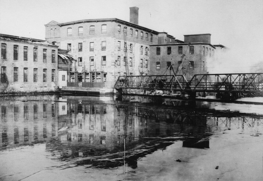 This photo just upstream from the dam and the former pedestrian bridge shows one of the mill buildings being demolished in the mid- 20th Century.