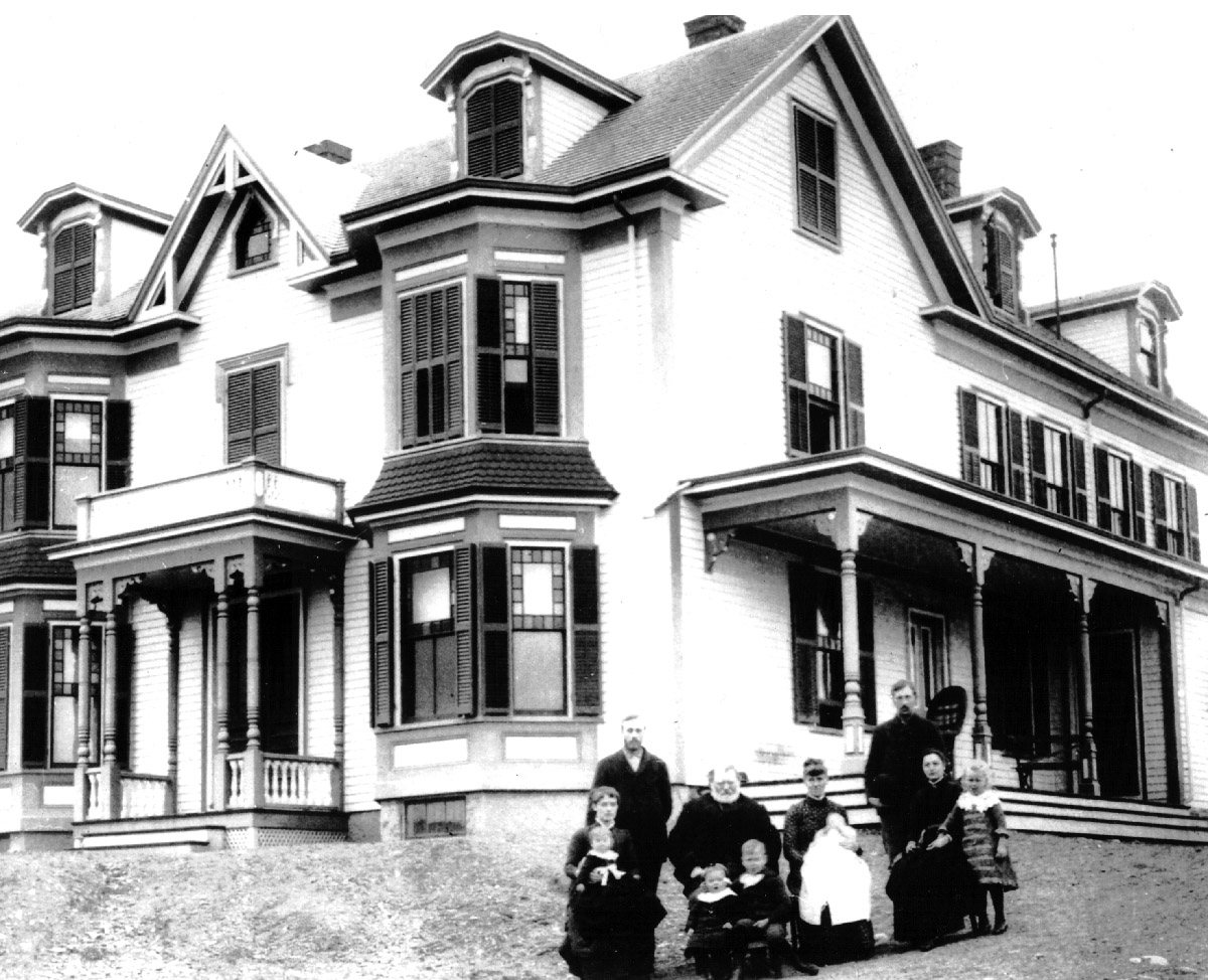 The Perley family and farmhouse at 387 Linebrook Rd. This picture is believed to have been taken in 1888. Standing: David Sydney Perley (2-21-1862) Seated in front: Louise Hart Perley (9-5-1865) On her lap: Marion Perley Jenks (1-7-1888) Seated: David Tuller Perley (1-17-1824) Seated in front: Bertha Perley Moulton (10-18-1886) Chester Garfield Perley (11-13-1881) Seated next to David T. Perley: Elizabeth Lavalette Perley (2-15-1857) On her lap: Harrison Otis Perley ( 9-30-1888) Standing: Roscoe Damon Perley (8-11-1864) Seated: Carrie Sophronia Perley (10-18-1865) Standing: Mabel Perley Charlton( 8-19-1883)