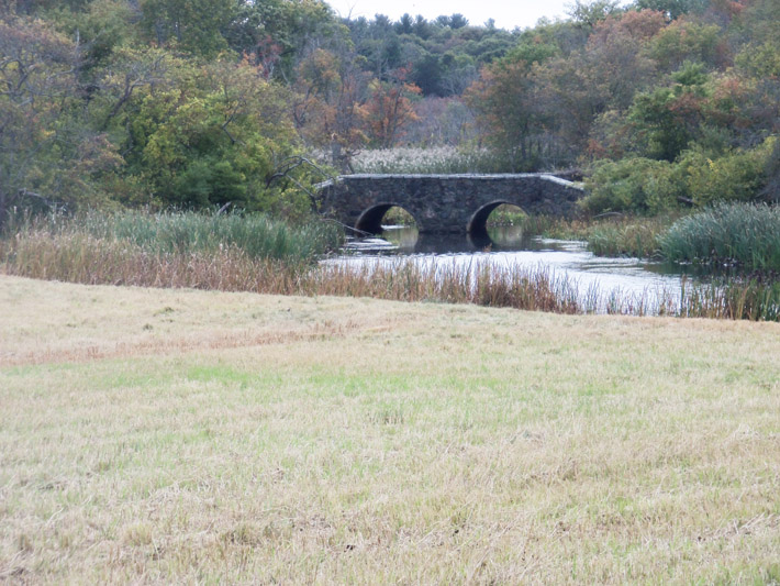 View of the simulated stone arch bridge from a field section of the trail near the parking lot.