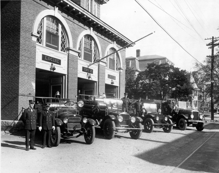 Fire station, with early motorized fire vehicles. The house behind it was moved one lot back.