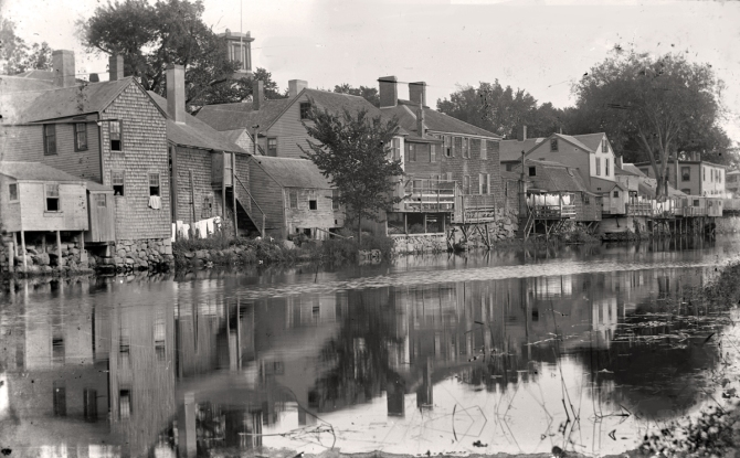 "A view of the rear of the buildings on South Main Street, just below the dam was known as ""Little Venice."" Photo by George Dexter, circa 1890."
