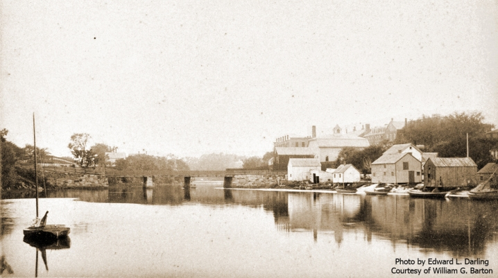 """William J. Barton Wrote, """"This is Water Street from Summer to Green Street, Ipswich, Mass. For a long time it was called """"Clam Shell Alley."""" The old wooden bridge in the distance was condemned, and a new stone arch bridge was built in 1894. For several years, I have been the last living man who worked on the bridge (not for pay). I helped my father as a boy working on wooden arches that held the granite in place. The Ipswich County House (House of Correction) is at the extreme right of the picture. My father, William E. Barton, had a Massachusetts Bay pilot license, and he piloted the rock sloop loaded with granite to build the new stone arch bridge. The river is not to deep."""" Photo by Edward L. Darling. Photo by Edward K, Darling."""