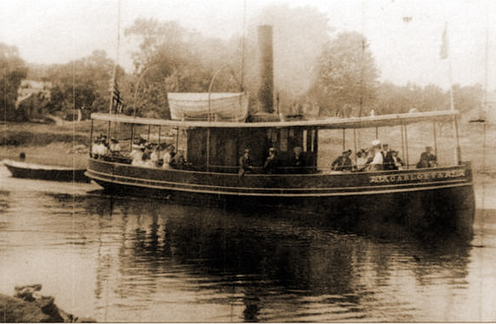 """William J. Barton wrote, """"From Brown's Wharf, the steamer Carlotta, a local steamboat owned by Nathaniel Burnham and Charles W. Brown sailed daily and carried passengers on the Ipswich River and Parker River. The Carlotta also was used as a tug boat for towing vessels up and down the river. The Carlotta carried 200 passengers with Captain Burnham as captain, plus an engineer and deck hand. Her stops on the daily trip were at Little Neck for 10 cents. The Ipswich Bluffs, 15 cents, Grape Island 20 cents, and the complete round trip to the Parker River at Newbury for 40 cents.It was very pleasant, about 12 miles. Before the advent of the electric cars and the automobile, people took advantage of this clean and pleasant way to travel. Various organizations on moonlight nights would run excursions. Among them were the Ottawa Club, a popular group of young ladies, and a musical organization known as the Ipswich Fife and Drum Corps. The Drum Corps would march from the center of town to the wharf, followed by a large crowd. At about 7:30 pm the Carlotta would sail. The drum corps played music all the way over to the Parker River, where they would run a dance. Refreshments could be purchased at the Pavilion. It was always high tide at eleven o'clock on a full moon, so they would start the return trip home. There was no music on the return trip. Every one would cuddle up to someone on the steamer as it was cold in the early morning, and enjoy the full moon. After all, that was what this excursion was run for. This was a wonderful thing to have the Carlotta running on the Ipswich River and Parker River. Everyone enjoyed the river. Howard C. Dodge of 4 Hovey St. had 20 boats to let that two or three could row, and some Sundays he would have to hire some boats of the clammers to take care of his customers. There was a hotel at Little Neck. The Ipswich Bluffs was one of the first places along the coast where you could have a wonderful shore dinner. At Grape Island they ran an exc"""