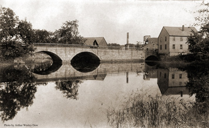 """The County St. Bridge In 1673, a fulling mill was built here and a grist mill in 1715. It is believed a grist mill was in operation here until at least 1872. As early as the 1720's this location was used as a wharf, and soon thereafter a shipyard was established. The town voted on March 11, 1861 to build this bridge due to the roundabout way people were forced to travel with the many heavy loads heading to and from the wharves along the river. Prior to the dam being built water power for the early mills here was generated largely due to the Falls, There is still remnants of a dam here today. In 1863, a mill was built at this location to produce yarn, and within 5 years it was producing hosiery. The mill complex was eventually used as a box factory and a warehouse before being torn down about 1920. During the 1870's Ipswich was receiving shiploads of corn, carrying as much as 3,000 to 5,000 bushels at a time. For many years a sawmill was in operation here. The first one is believed to have been in use by 1652, and the last standing sawmill here was in 1902, although not in use at the time. (from """"The Industrial History of the Ipswich River."""") Photo by Arthur Wesley Dow"""