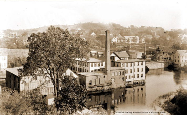"""William J. Barton wrote, """"The Ipswich Woolen Mill, County Street, Ipswich MA, sometimes called the Lower Mill. Beyond the County Street bridge and Cove is Turkey Shore Road.To the right of the chimney is the Plouff house. The next long building was at one time a distillery where rum was made, later a tannery around 100 years ago. The three houses now belong to Mrs. Chester Bolles. Across the bridge at the right end of the mill is Canney lumber. Photo by Edward L. Darling."""
