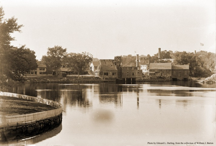 """View of the County St. mills from the Cove at Poplar St. Photo by Edward L. Darling. A Distillery for the manufacture of rum was located along Turkey Shore as early as 1765. It continued its operation until 1836, when it was sold and converted into a Tannery, which was still in operation in 1872. The riverbank that now hosts the Sidney Shurcliff Riverwalk was used as a campsite by Native American's to fish during the spring spawning. Two and three-masted sailing ships loaded and unloaded wares in the Great Cove, timing their arrival and departures with the tide. (From """"The Industrial History of the Ipswich River."""")"""