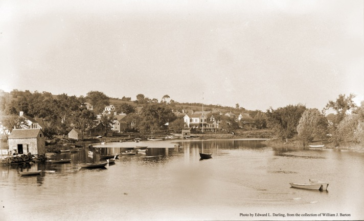 "William J. Barton wrote, ""The lower part of Ipswich River, Ipswich Mass from the Green Street Bridge. The first building on the left was a fish shanty. The three men who ran the fish market peddled by horse and wagon was Lewis Grant, Dennison Rush, called 'Dense'. and Charles Rush. Every day they boiled lobsters and one, almost a foot long, sold for 10 cents. All the children in the neighborhood would sit on ice chests over the water in rear of the building in all of the stream as the above men we thought were old fellows boiled a pot of crabs for us children. ""Happy Days!"" Next to the building was the best town landing on the river. There was no road beyond this building along the river in those days. The next little building beyond the fish shanty was used at one time by Robert (Bob) Gone, and I think by my father to keep fishing gear. They and a crew of men fished along the South Shore for herring. The nice house with the flag pole was the home of Howard Dodge (now Raymond Dodge's home). The little building in front was a sand house. He sold sand to masons to make plaster. My father would bring a dory full of sand he would get on Ipswich bar for Mr. Dodge. One of these boats is anchored here, and is likely to be his."" Photo by Edward L. Darling"