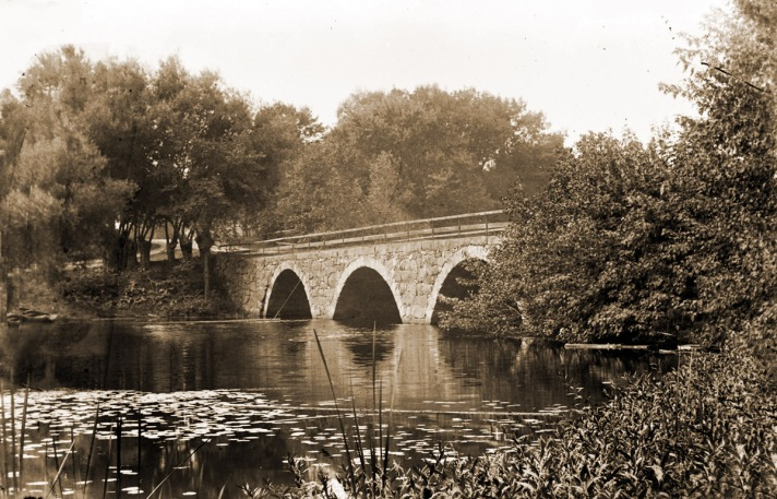 """Mill Rd. /Highland St. Bridge:Just upstream from the Mill Road/Highland St. bridge, an earlier bridge was built about 1667, but no longer exists. The current bridge was built between 1829 and 1832, with three stone arches. The bridge was severely damaged and closed after the Mothers Day Flood of 2006, and re-opened May of 2009. This site was first in use in 1697 as a fulling mill. In 1794. a carding machine and a picking machine were added. Sometime around 1857 it was converted to an Isinglass Mill. This mill was in use until approximately 1912. In the late 1880's, it was producing 100,000 pounds of isinglass annually. The building was torn down in 1919, but portions of the foundation and sluiceway can still be seen today. On the Hamilton side of the bridge, a grist mill was built at this location in 1697 and continued in operation until 1918. A saw mill was added circa 1750, and was also in operation as of 1918. By 1880, a cider mill had been added and was in operation until 1919, when the property was sold. During the year 1887, the cider mill consumed more than 10,000 bushels of apples, resulting in the production of 35,000 gallons of cider, and in 1918 the mill produced 60,000 gallons. After a fire in 1822, a new structure was built to house the grist and cider mill that is still standing today. From the bridge, you can see the remnants of the dam. The original dam at this location was built in 1697 in conjunction with the building of the fulling and grist mill. It was allowed to be built 3′ above the river's normal level. It can be assumed that it was torn down when the mills no longer operated at this location. (From """"The Industrial History of the Ipswich River."""")"""