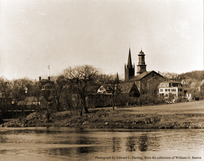William J. Barton wrote: This picture was taken from Turkey Shore Road from a point by Ausgustin H. Plouff's or Chester Bowles' house. On the extreme left is the Lower Mill, which at time was awoolen mill. Behind the barn on the left is the Ipswich Girls Seminary Building, and the North Congregational parish house. On North Main St. is the flag pole at the soldiers monument where each morning since 1910 someone from the Post Office would put up the flag. The flags were furnished by the weather bureau, telling what the weather would be. In back of the trees can be seen the Damon Building on County St. The white house sat on the side of the Episcopal Church. Next are the steeples of the North Congregational and Methodist churches.The white house on the right with the mansard roof was built by William Willcomb, owned afterwards by his daughter Mrs. Carrie Angus.The Methodist Parsonage at 27 County St. is to the right. Photo by Edward L. Darling.