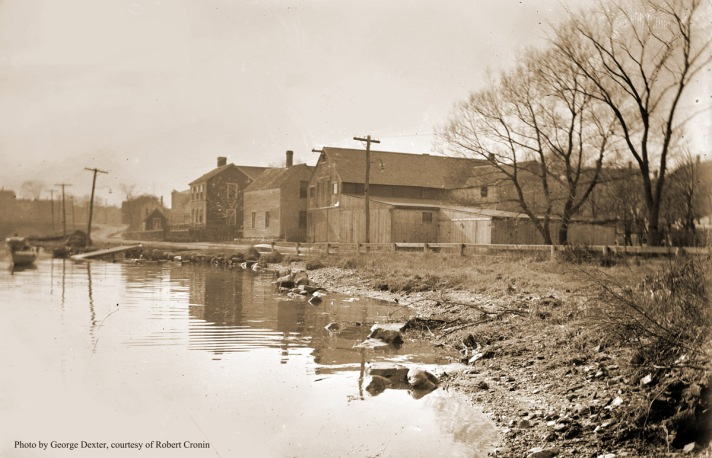 """William J. Barton wrote, """"What is now Water Street, Ipswich, Mass. from right to left: Howard C. Dodge boat house, Ephraim Grant house. The boat house burned down,and the Grant house was torn down around 1958. The next house is still standing on the lot this side of Summer Street house. Beyond on left are fish houses, and clam houses running from Summer St.on what is now Water Street, once called """"Clam Shell Alley."""" Photo by Edward L. Darling"""
