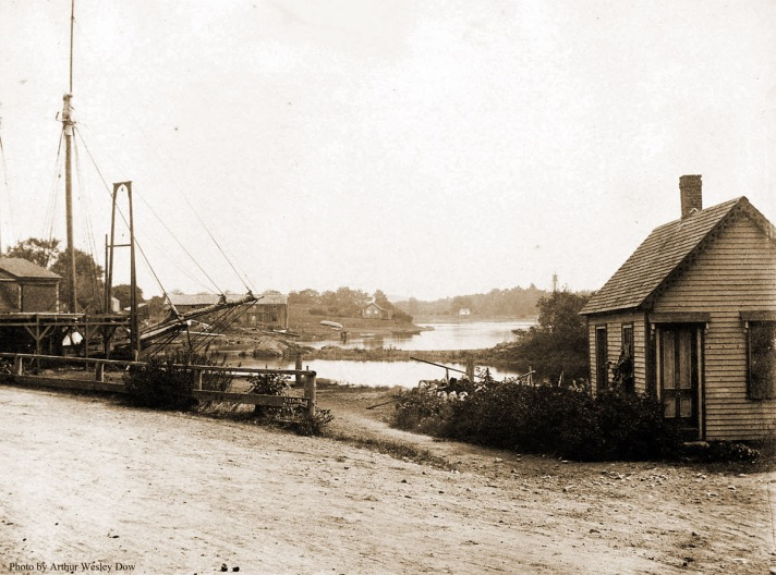 "Alice Keenan wrote, ""This picture shows the Town Wharf circa 1890, and the masts of a coal schooner unloading in front of Brown's wharf and warehouse. In the background standing well beyond Agawam avenue is the Edward Choate shipbuilding yards. Here he built among others: ""The Lucy Cogswell"" in 1868; ""The Fred Gray"" in 1869; ""The Mattie F"" in 1875 and what has to be the most photographed excursion boat of them all, ""The Carlotta"" in 1878. The boats were launched down a tiny little railway that ran into the river and whose rails could still be seen a dozen or more years ago before they silted over. In the background is the tiny cottage that later served as the summer home of Miss Claretta Rogers whose family then owned the old Newmarch house on Agawam avenue and the entire sweep of acreage from the river bank back onto Newmarch street. In the center of the picture is the ever-present ""Ringbolt Rock."" This ancient guardian of the tiny harbor was so named because of the giant iron rings that somehow or other were fastened to its slippery surface and helped pull the boats around the point when the going got sticky. Similar iron rings dotted Nabby's Point and other spots along the river and remained in place until gathered up in the great scrap metal drives of World War II."" Photograph by Arthur Wesley Dow."