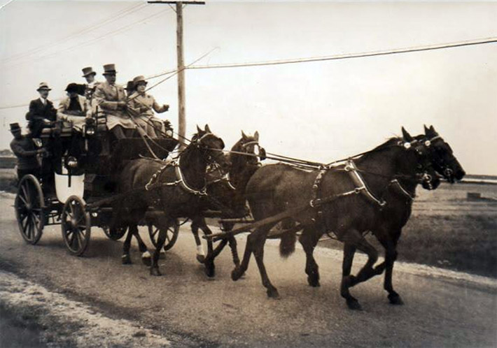 Visitors arriving by stagecoach on the Plum Island Turnpike
